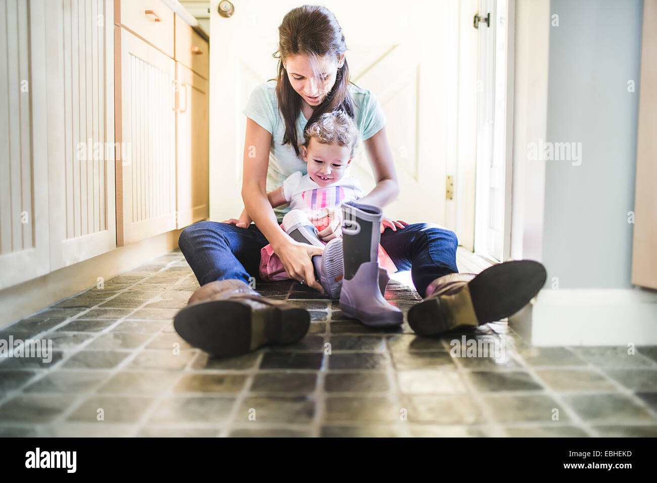 Mother and daughter putting on boots in kitchen - Stock Image