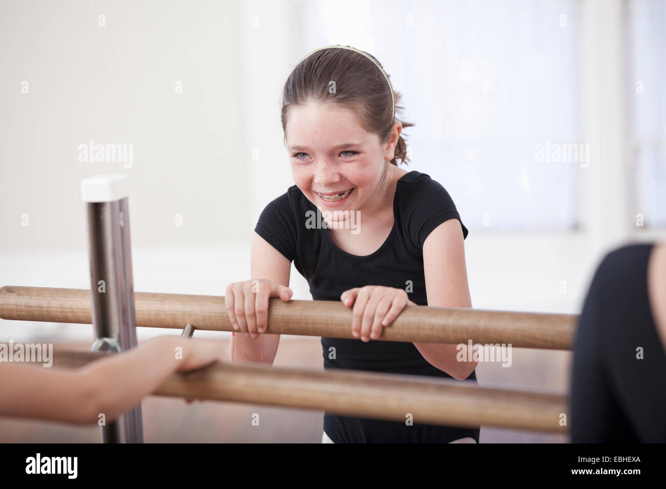 Girl laughing whilst at the barre in ballet school - Stock Image