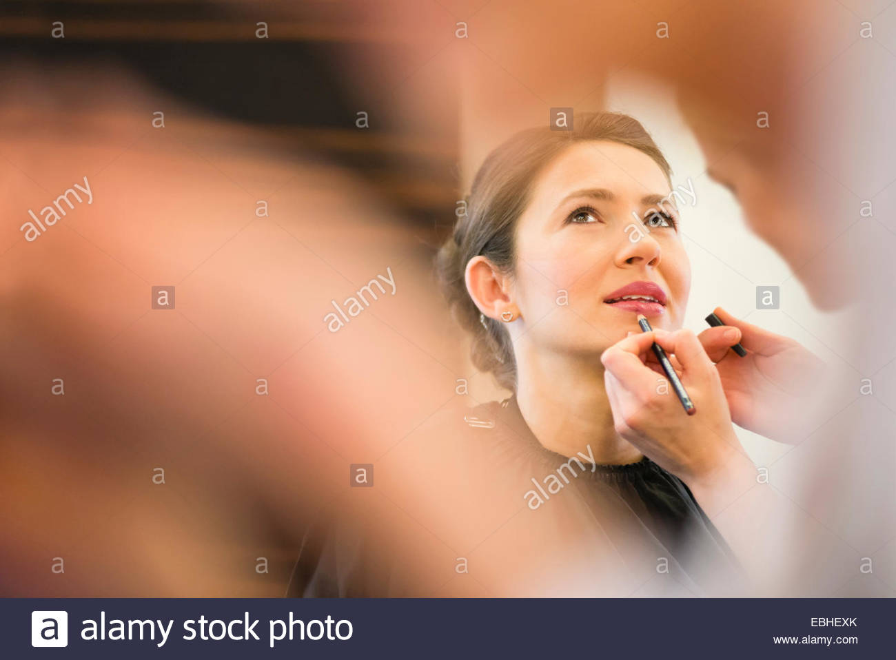 Female friend applying lip liner to brides lips - Stock Image