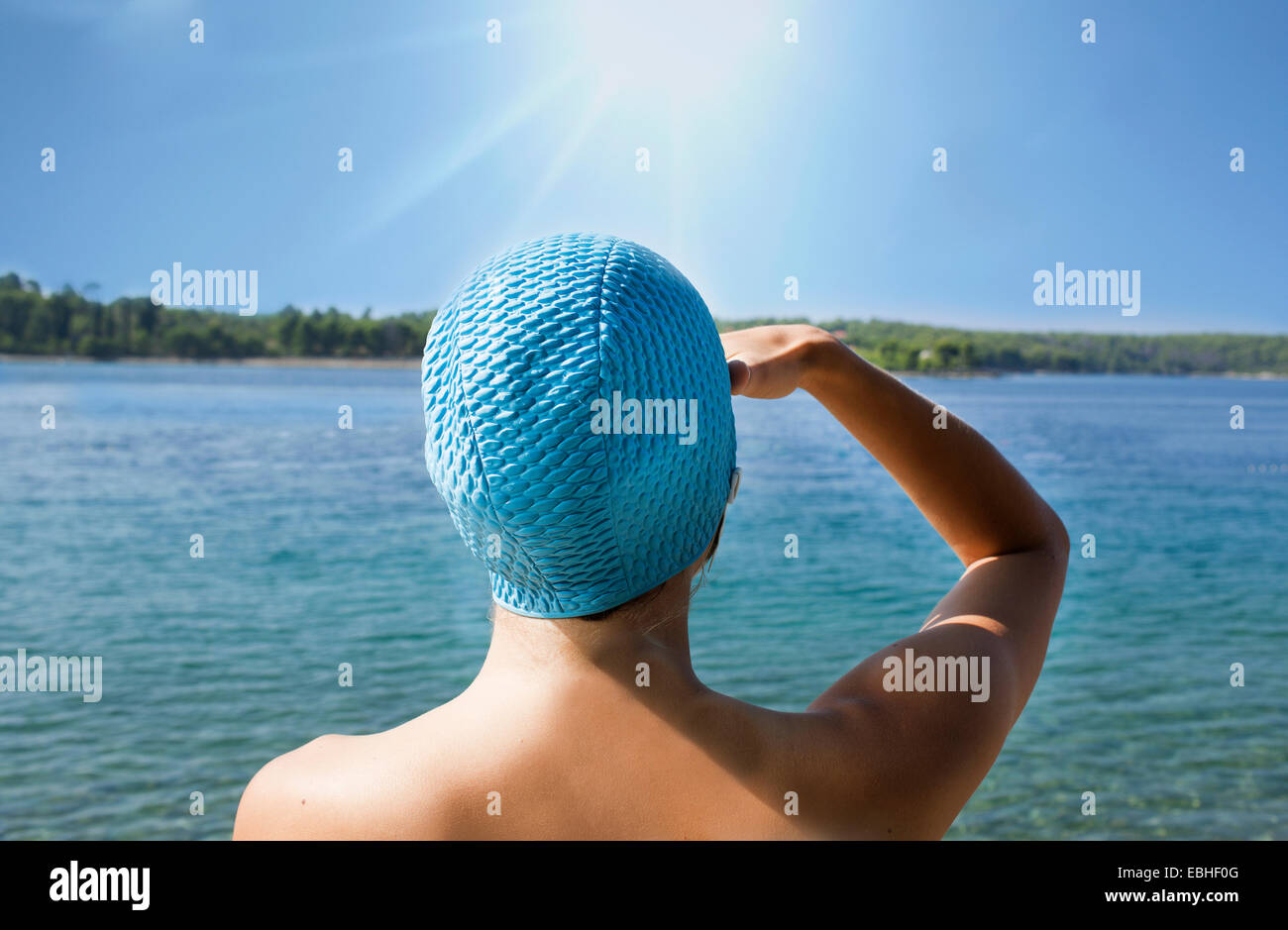 Rear view of young woman in blue swimming cap gazing out to sea, Milna, Brac, Croatia - Stock Image