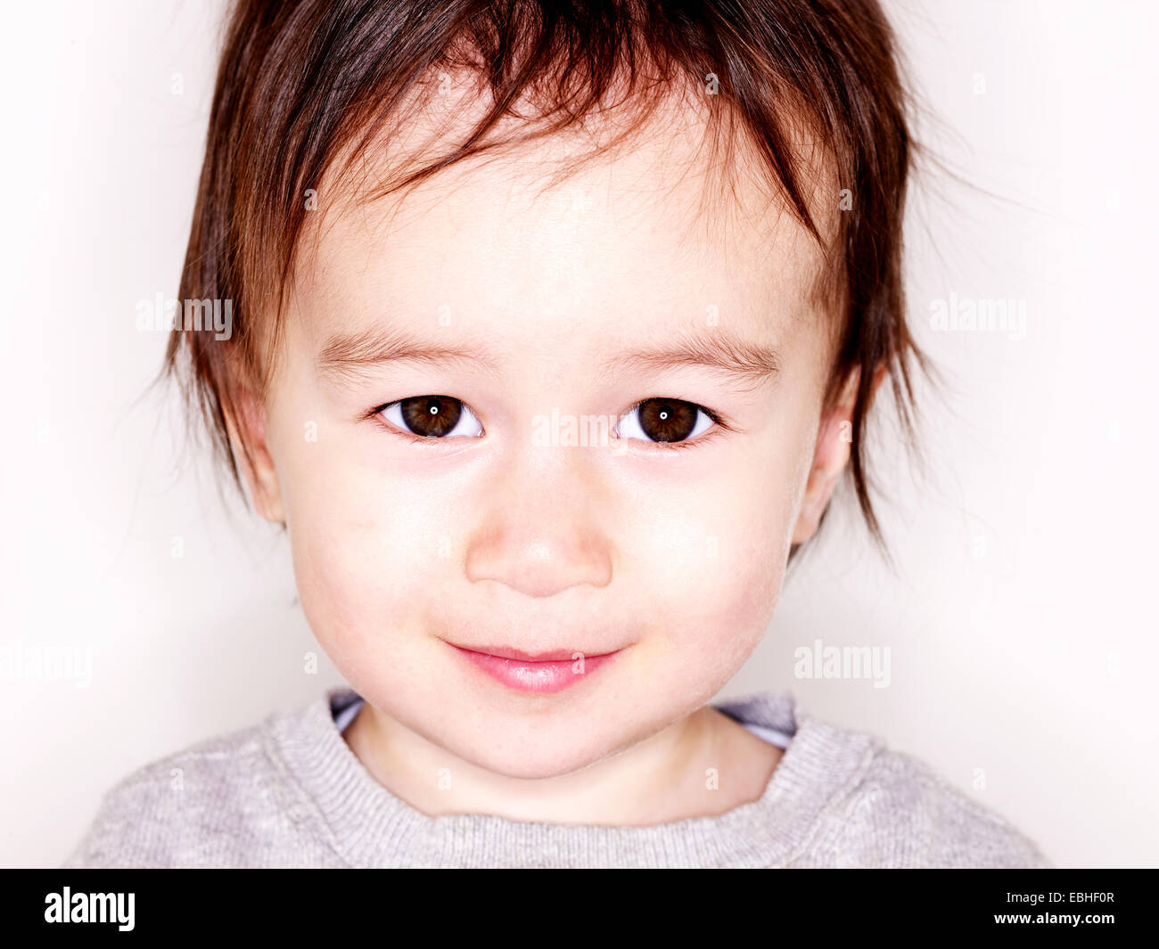 Close up studio portrait of smiling male toddler - Stock Image