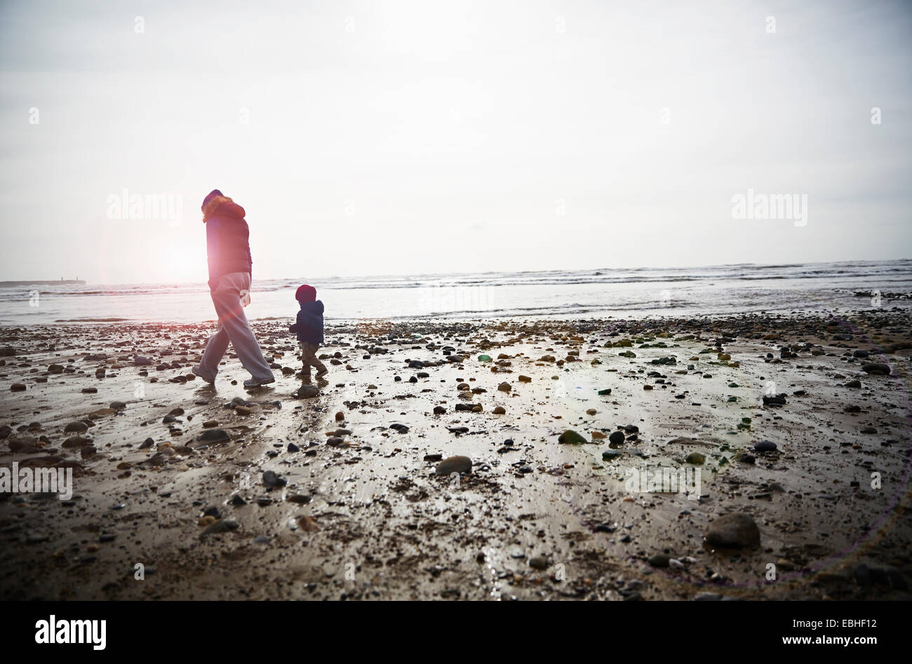 Male toddler and mother strolling on beach - Stock Image