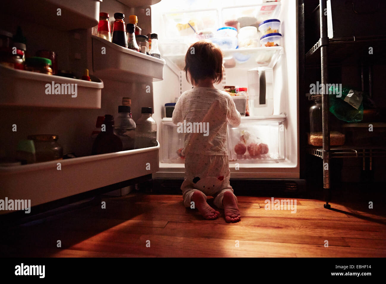 Rear view of male toddler kneeling in front of open fridge at night - Stock Image