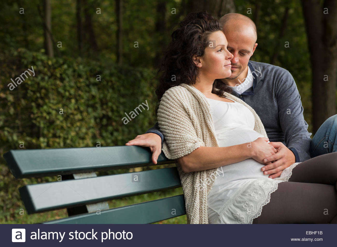 Pregnant couple caressing belly on park bench - Stock Image