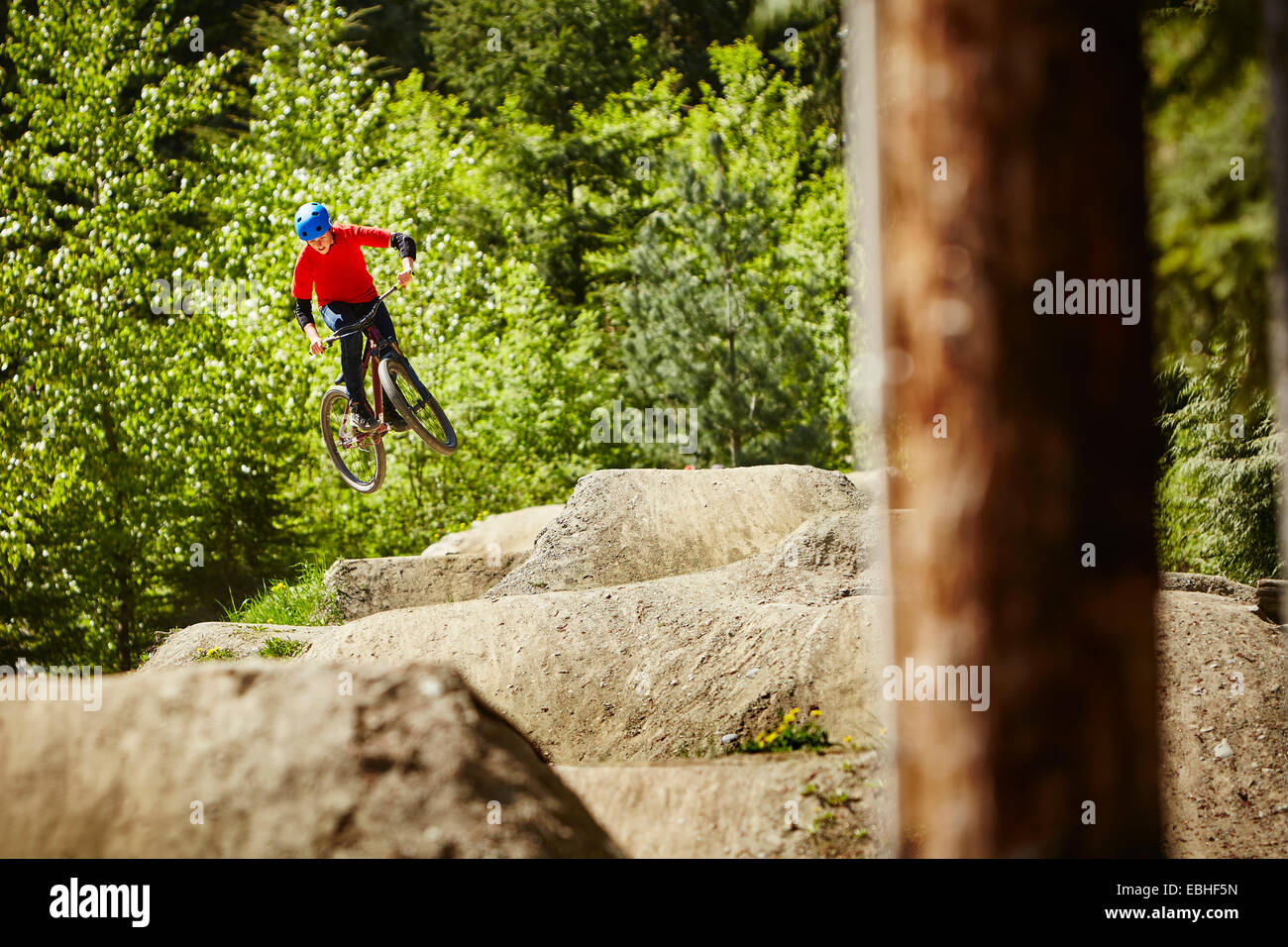 Young female bmx biker jumping mid air from rocks in forest - Stock Image