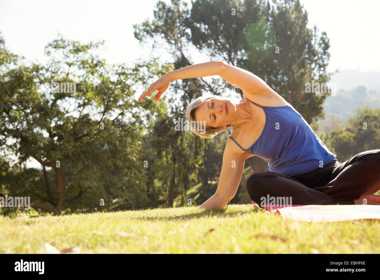 Mature woman practicing yoga in park - Stock Image