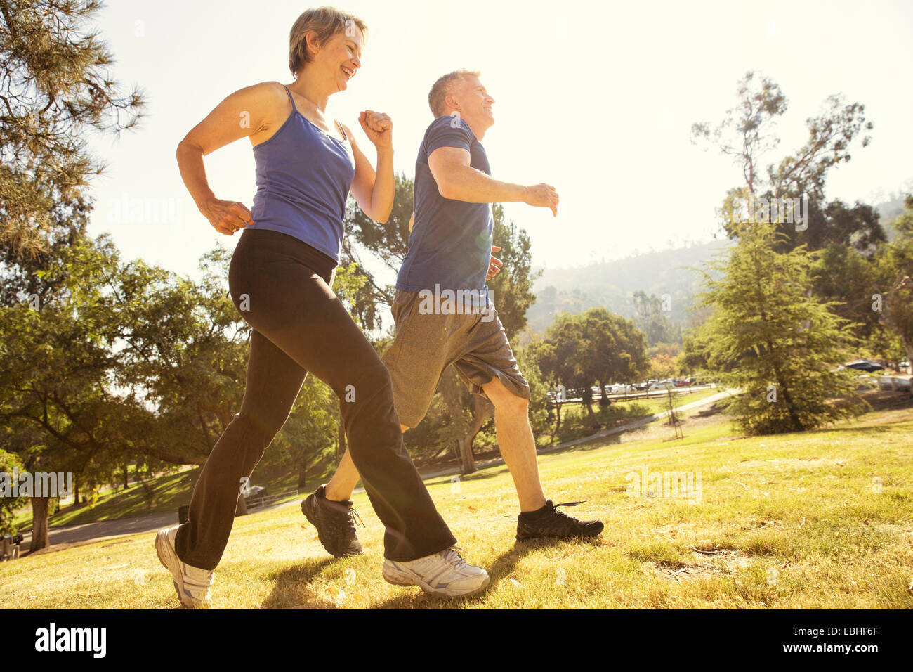 Mature couple power walking in park - Stock Image