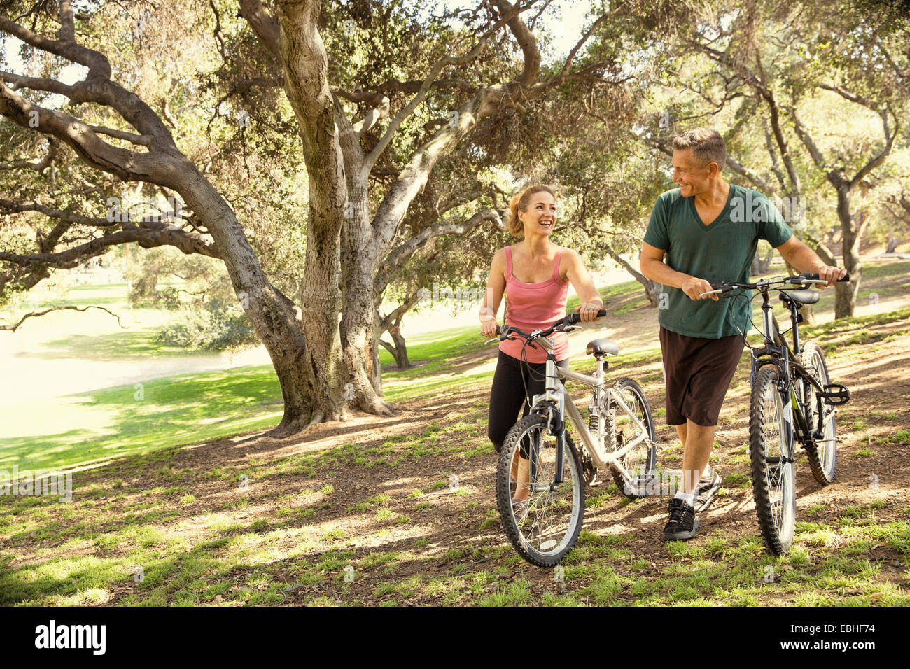 Mature couple chatting and pushing bicycles through park - Stock Image