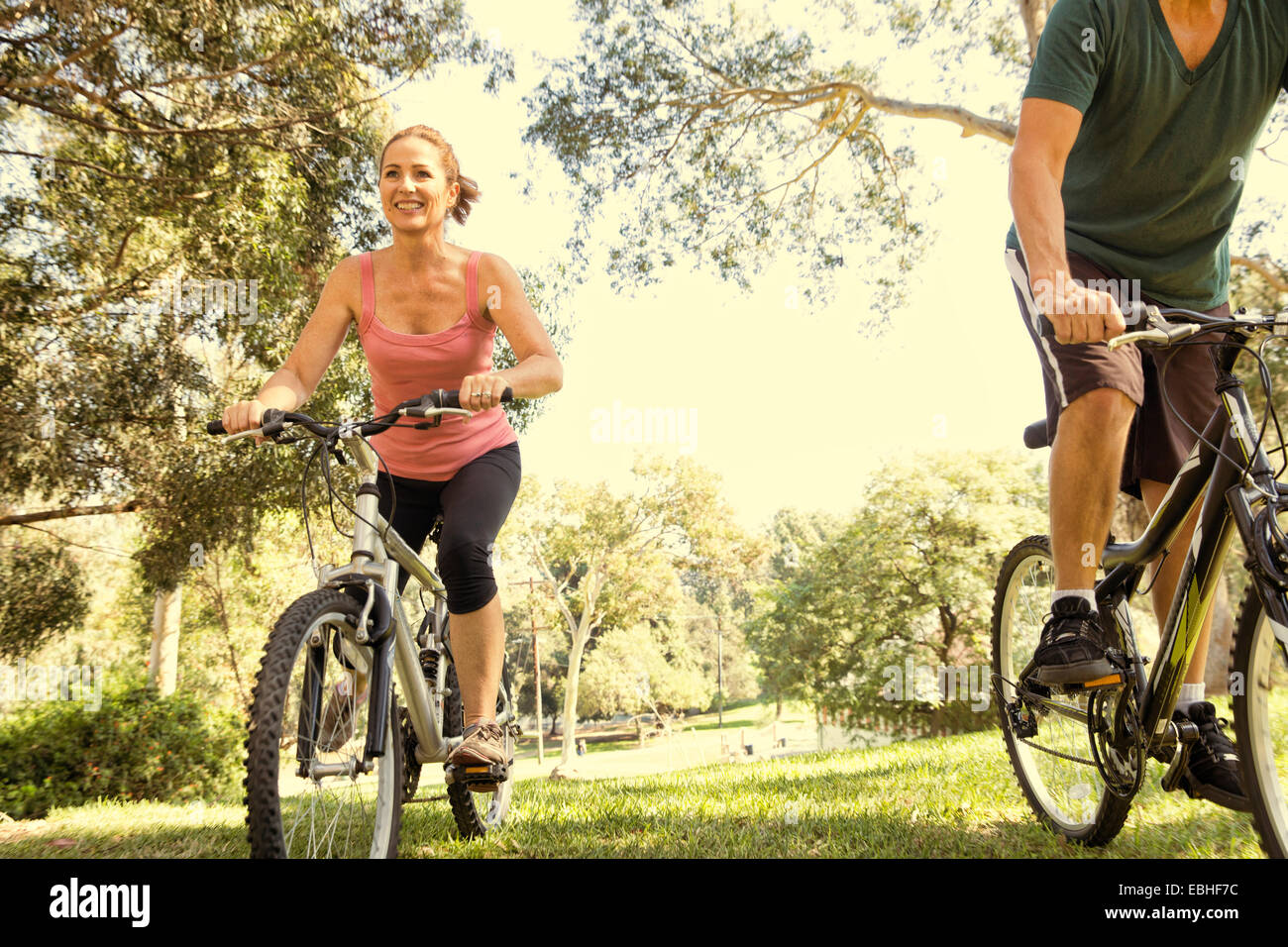Mature couple cycling through park - Stock Image