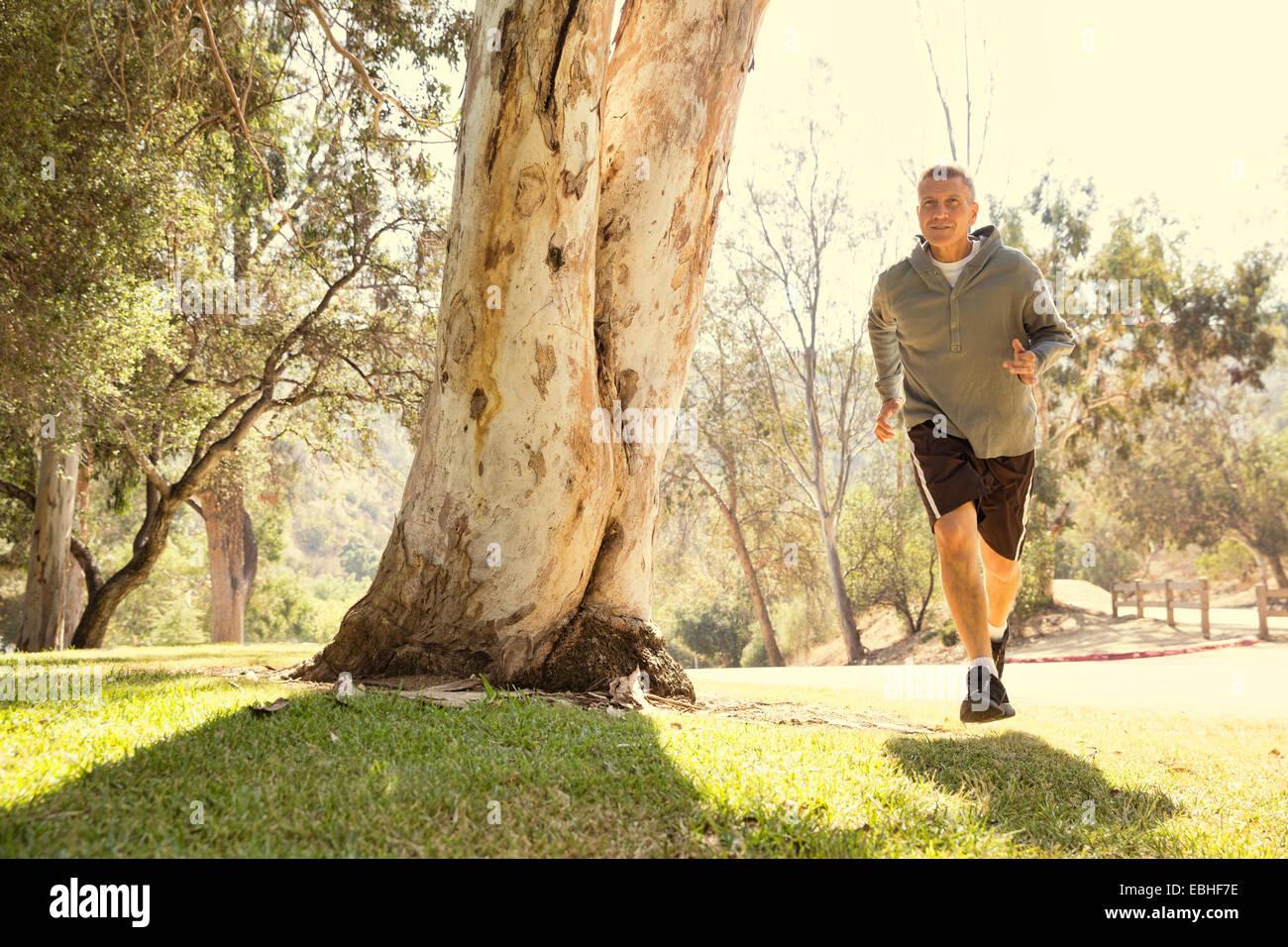Mature man running through park - Stock Image