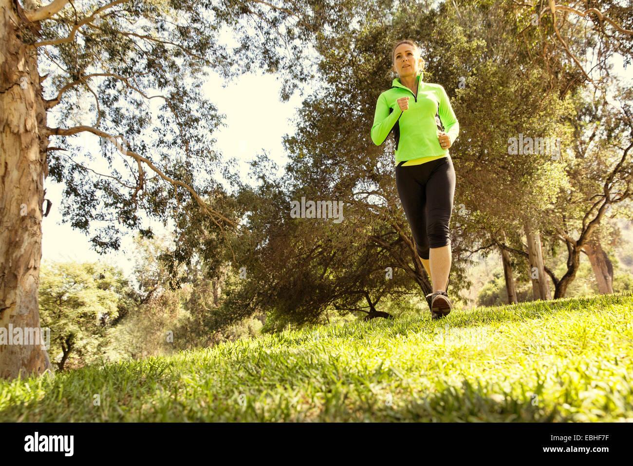 Mature woman running through park - Stock Image