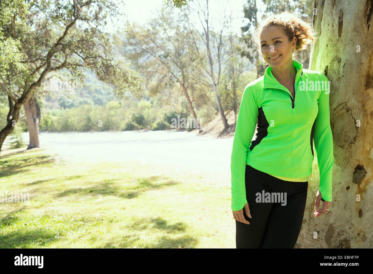 Portrait of mature female runner leaning against tree trunk in park - Stock Image