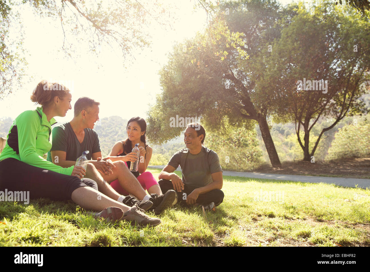 Four mature male and female runners sitting chatting in park Stock Photo