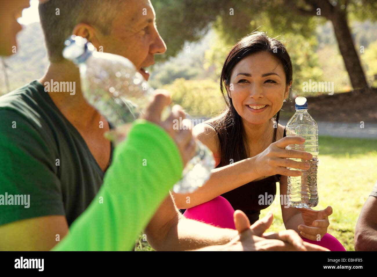 Mature male and female runners taking a water break in park Stock Photo