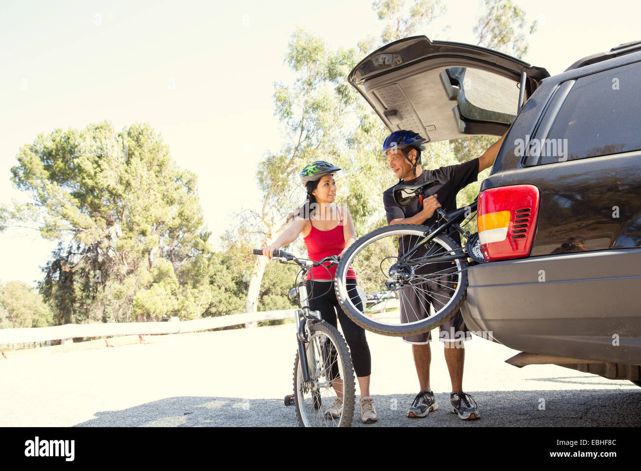 Mature couple removing bicycles from car boot in park - Stock Image