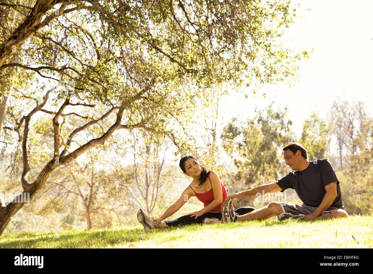 Mature running couple warming up touching toes in park - Stock Image