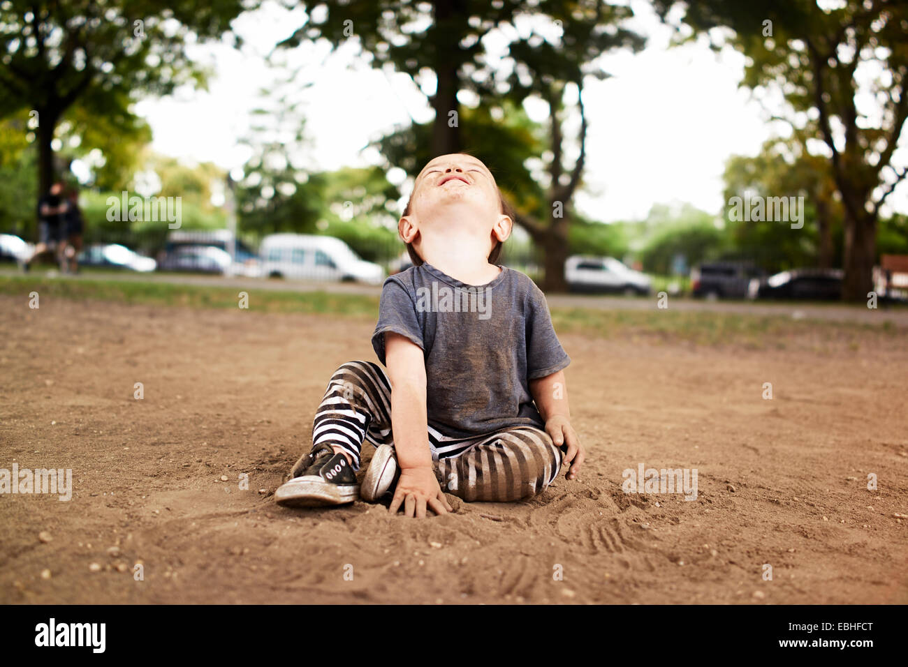 Male toddler sitting in park looking up - Stock Image