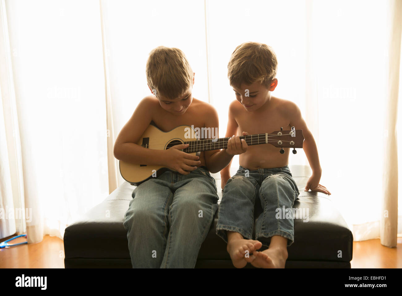 Brothers playing guitar at home - Stock Image