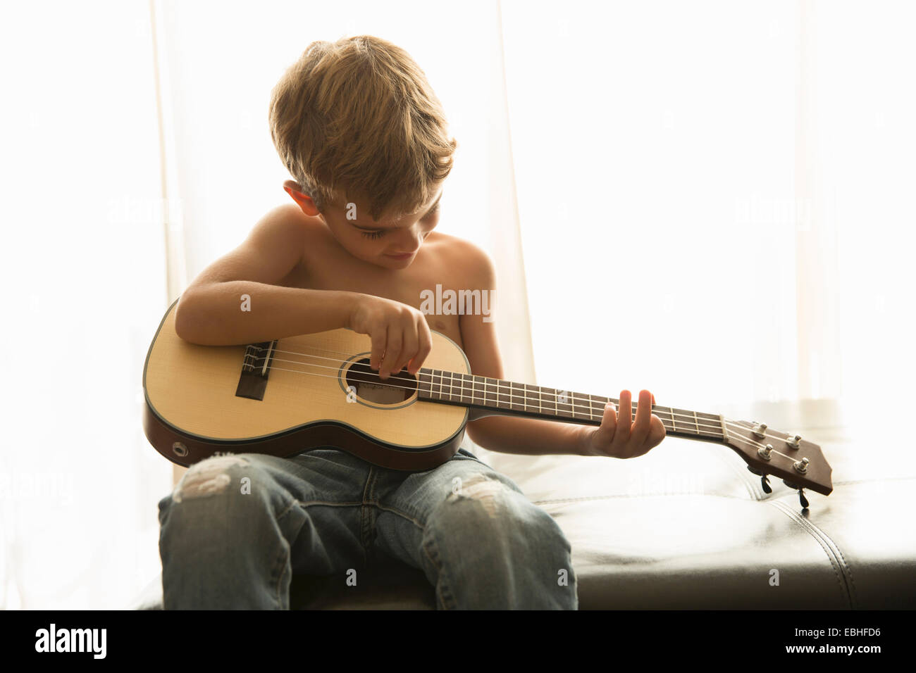 Boy playing guitar at home Stock Photo