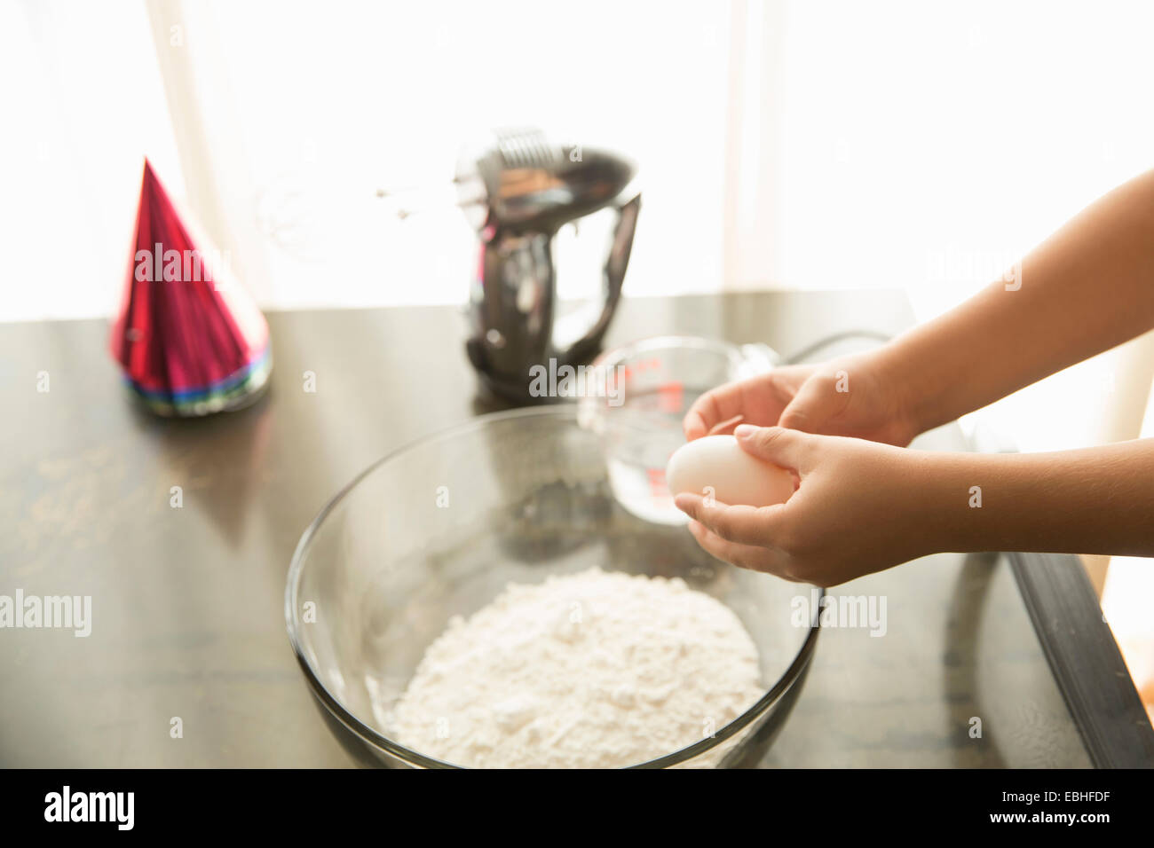 Hand holding egg over mixing bowl on table - Stock Image