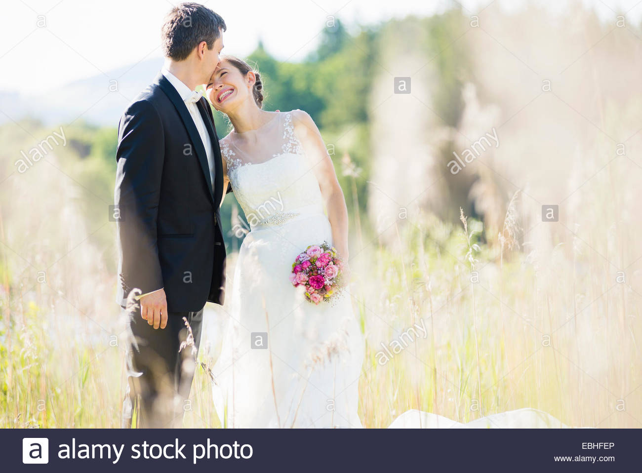 Candid portrait of bride and bridegroom in field - Stock Image
