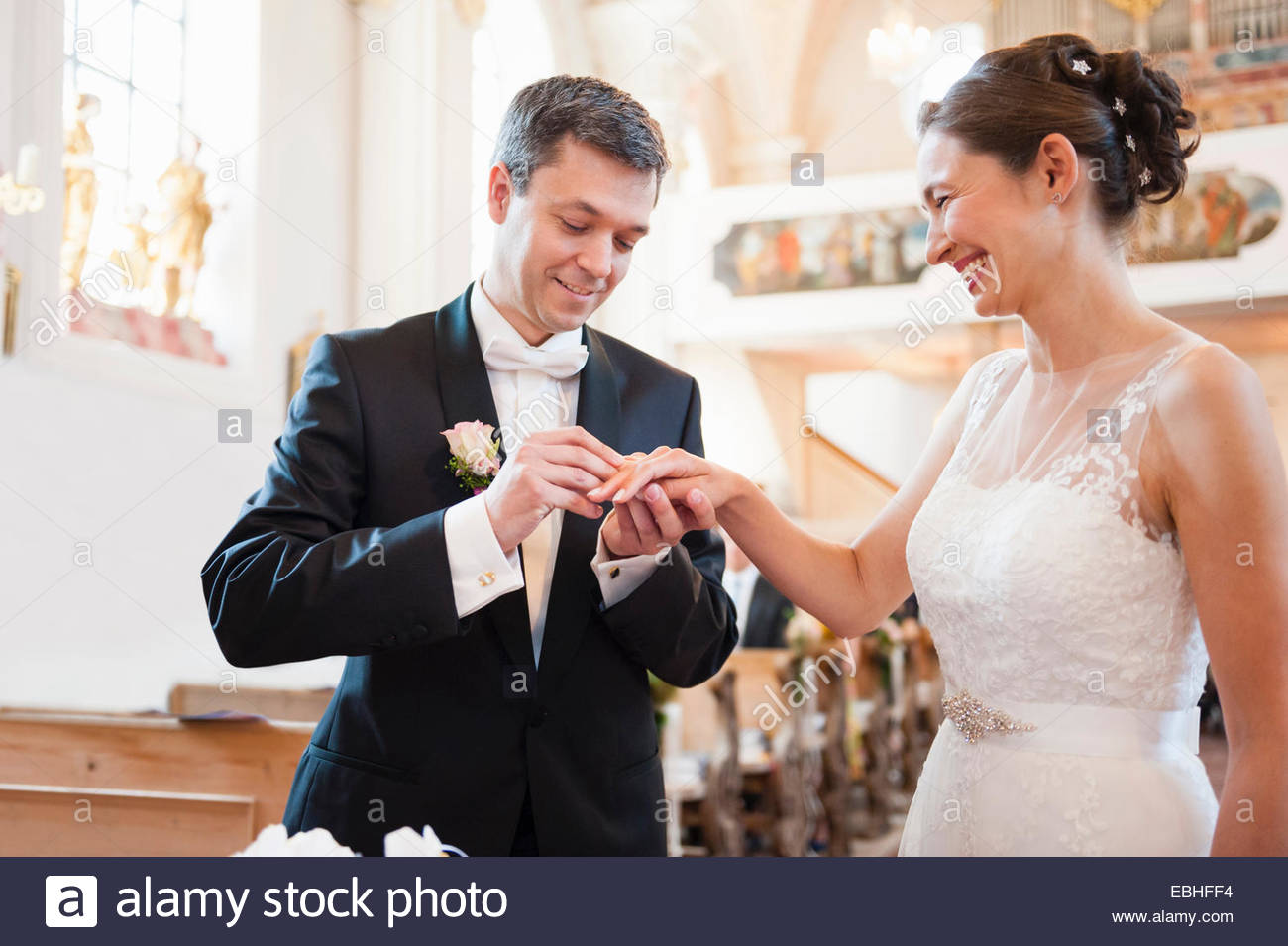 Bridegroom placing wedding ring on brides finger in church - Stock Image