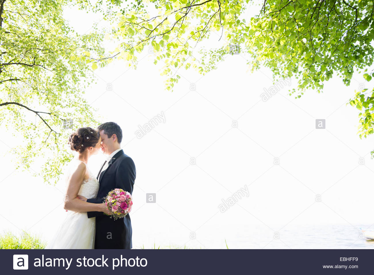 Romantic newlywed mid adult couple kissing in park - Stock Image
