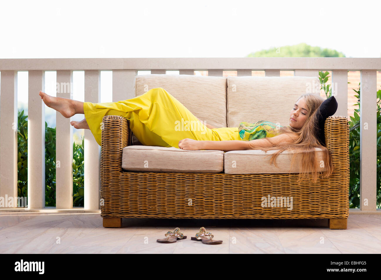 Young woman asleep on balcony sofa, Milna, Brac, Croatia - Stock Image