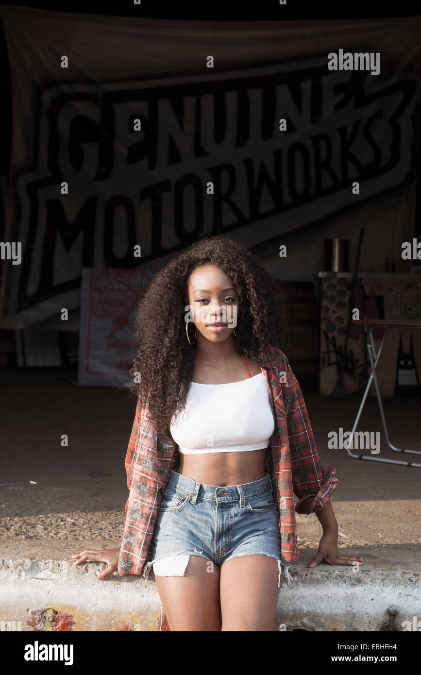 Young woman wearing cut off jeans and crop top - Stock Image