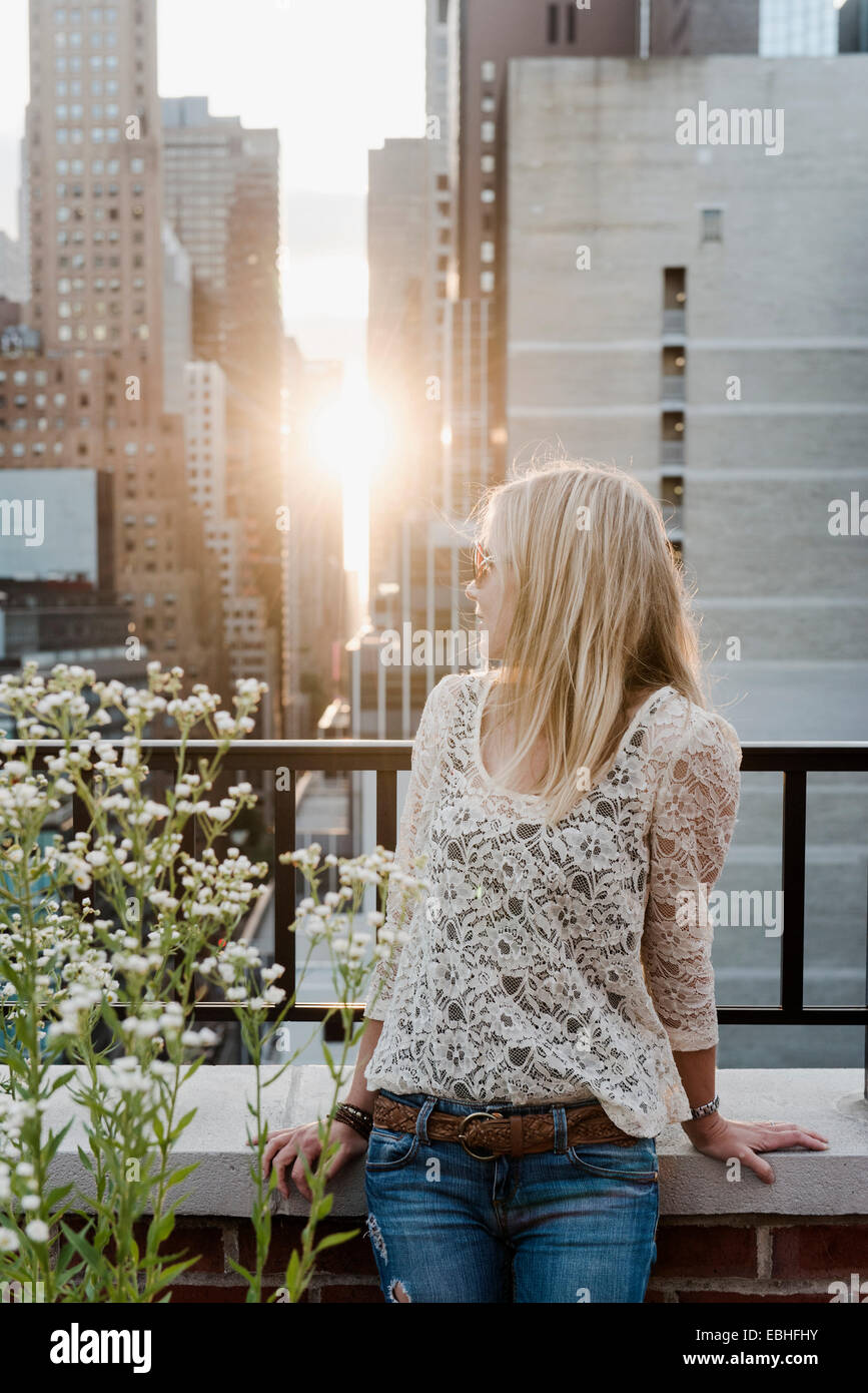 Young woman looking at city view over shoulder - Stock Image