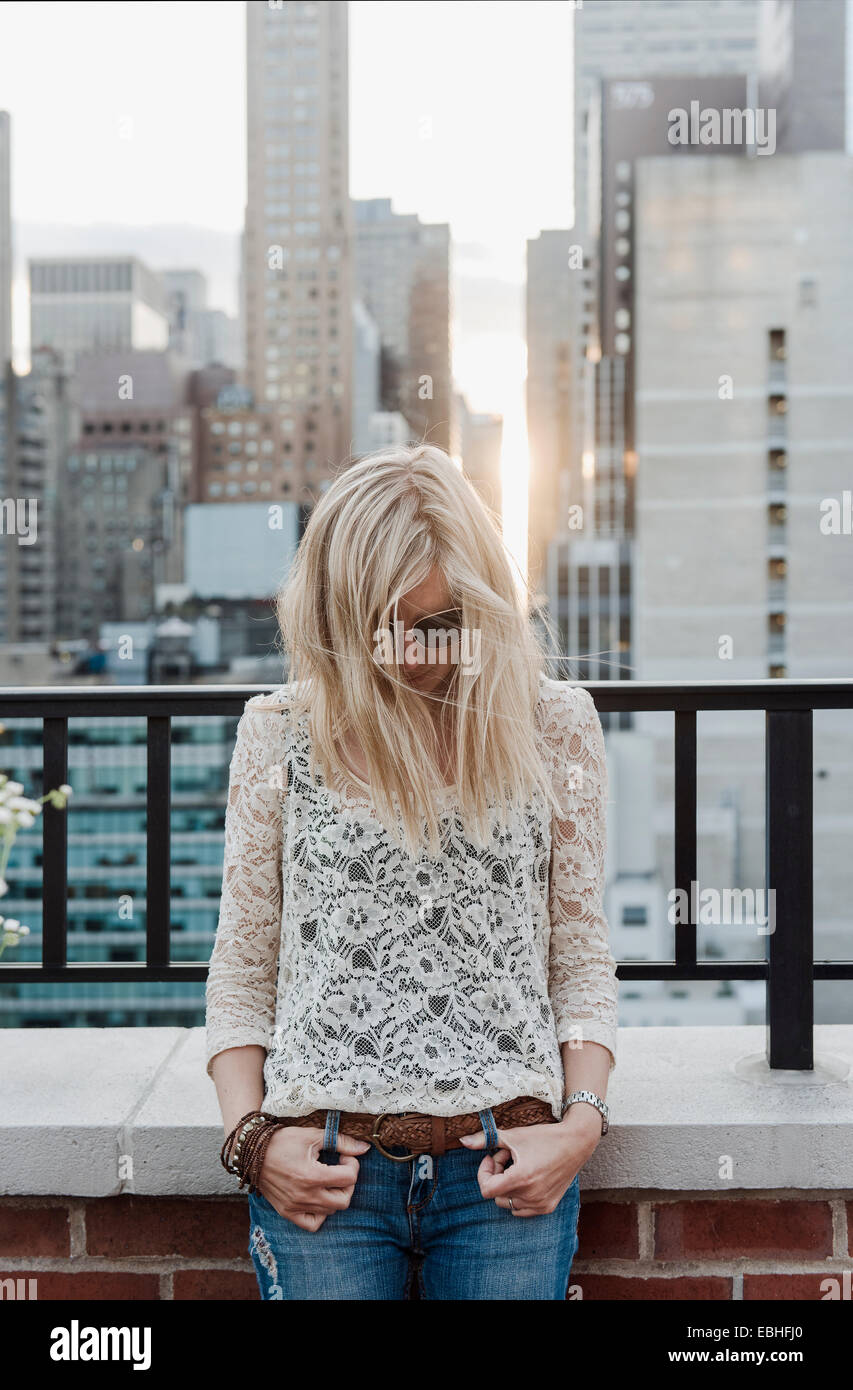 Young woman with city view in background - Stock Image
