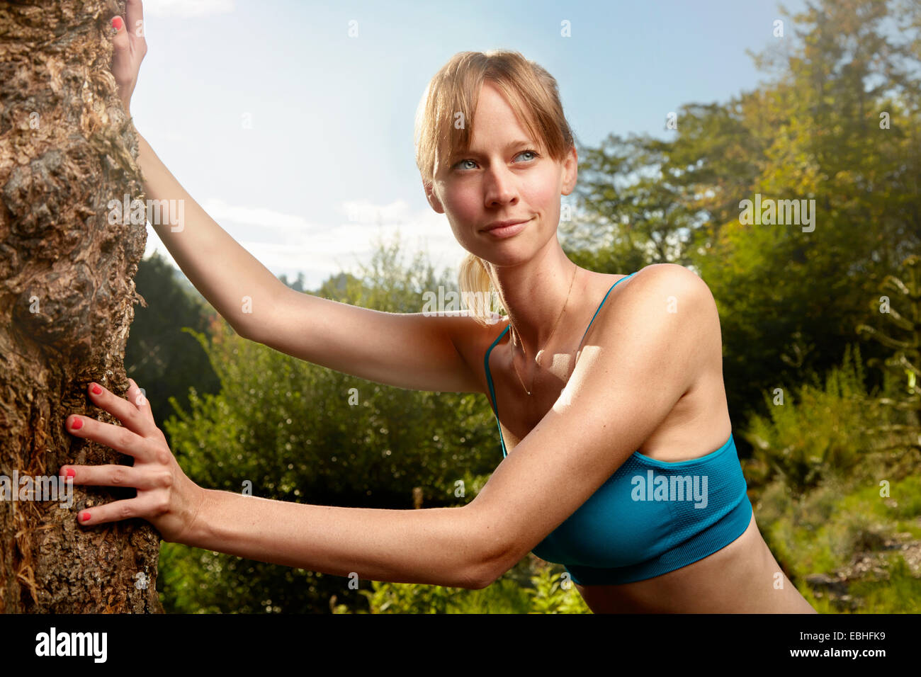Female runner leaning against rock in park warming up - Stock Image