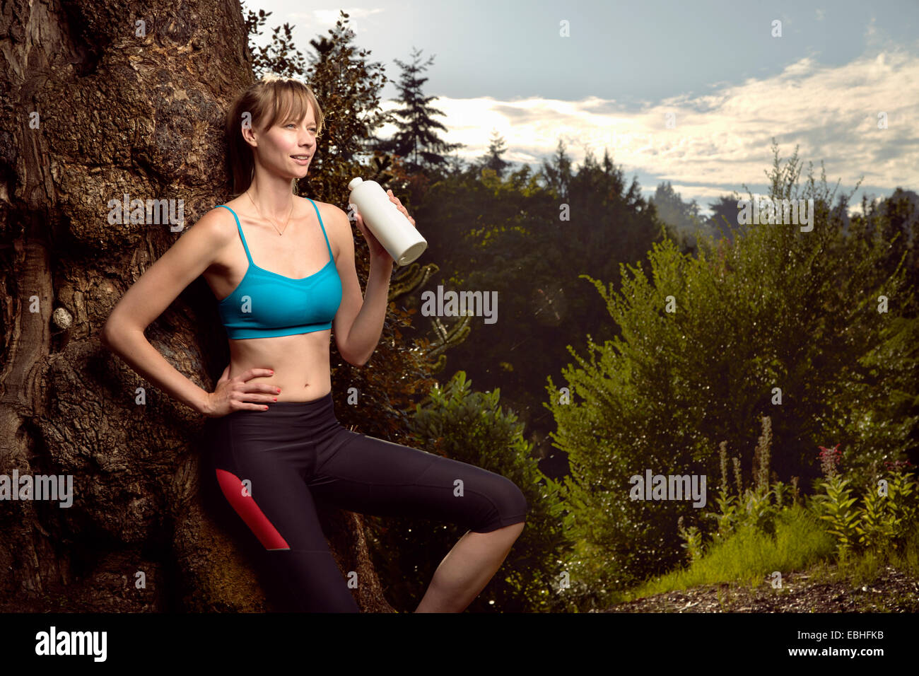 Female runner leaning against rock in park drinking water - Stock Image