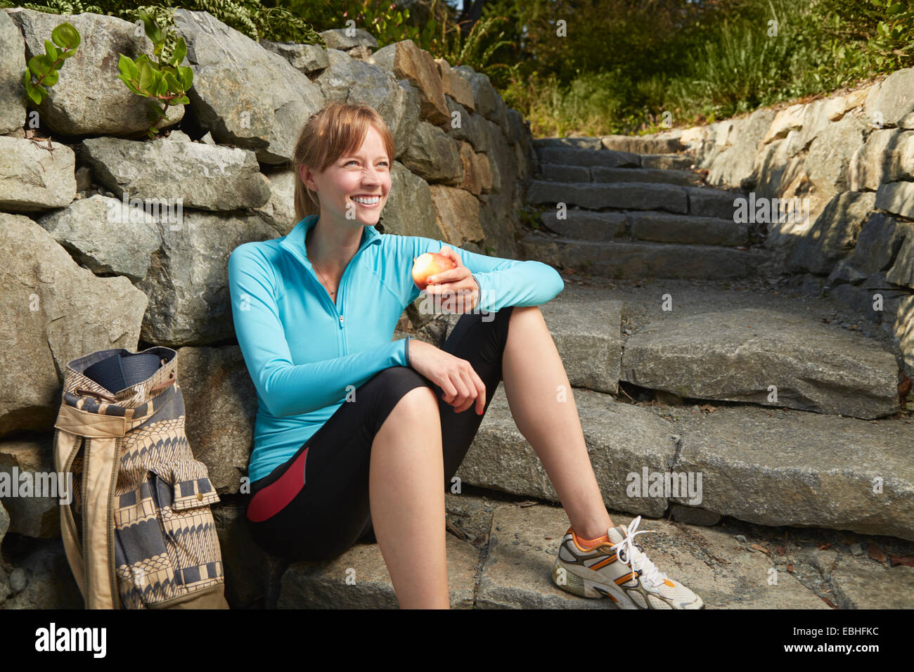 Mid adult female runner taking a break in park eating an apple - Stock Image