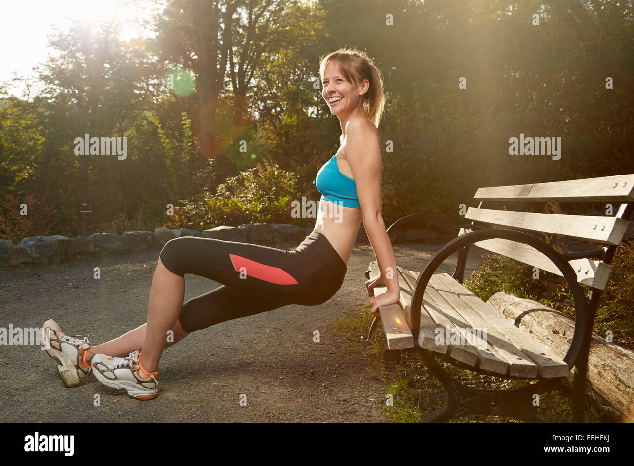 Female runner stretching against park bench - Stock Image