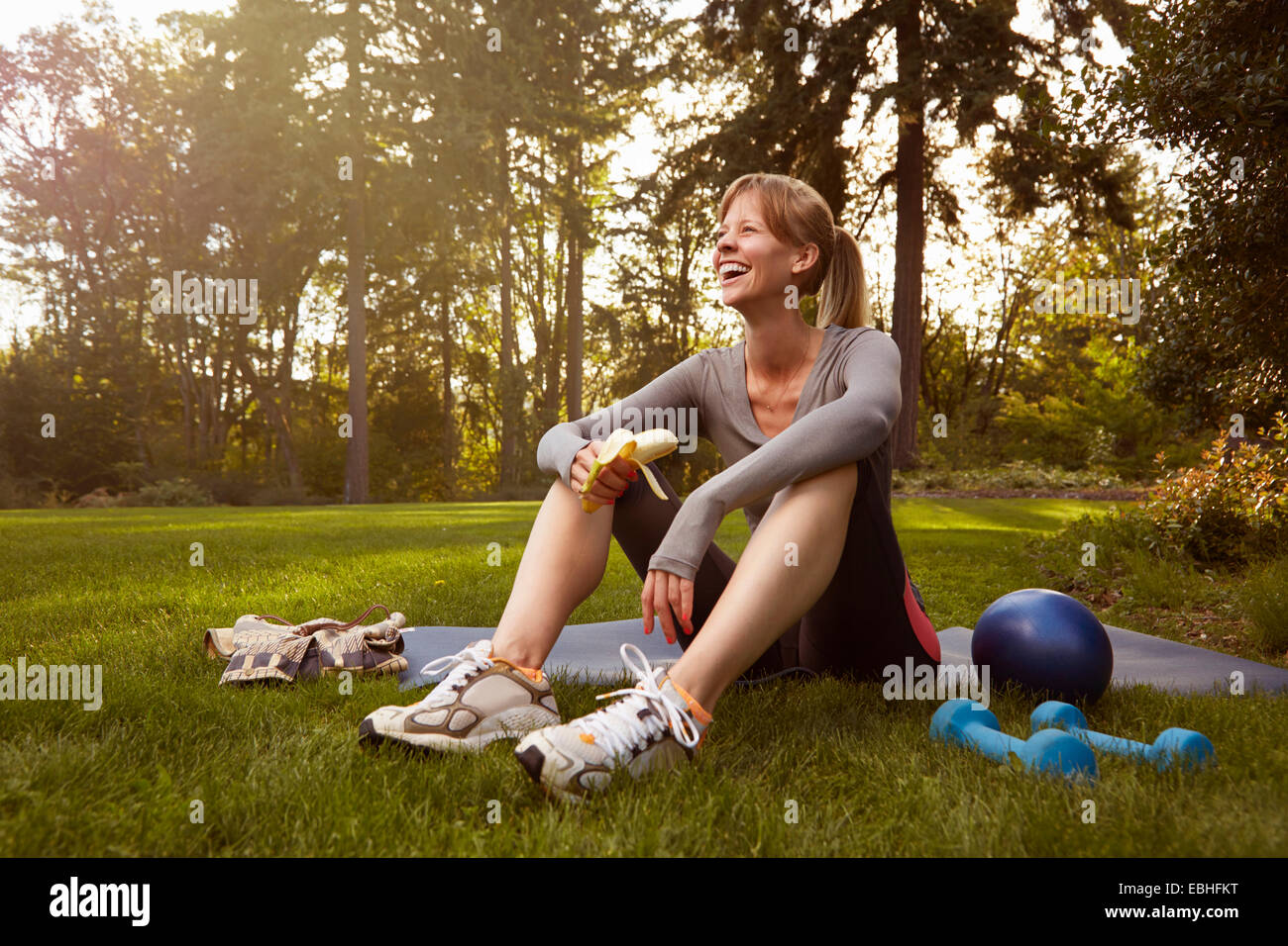 Mid adult woman sitting in park taking exercise break - Stock Image