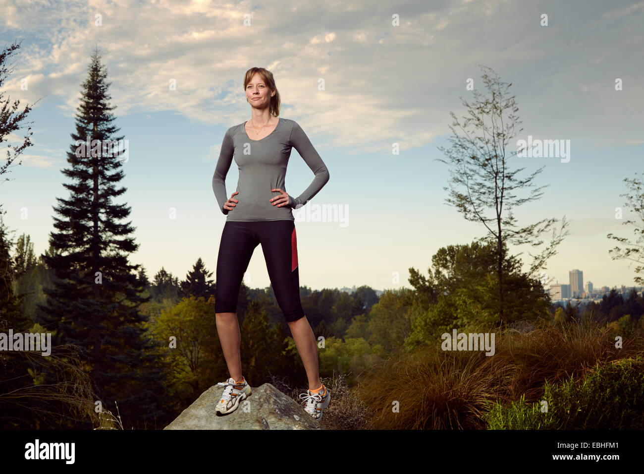 Portrait of female runner on top of boulder in park - Stock Image