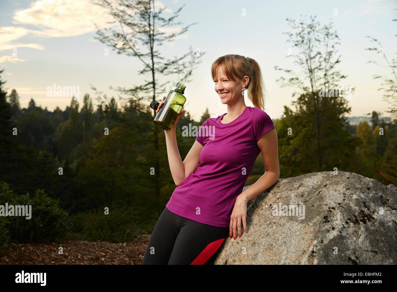 Female runner leaning against boulder in park drinking water - Stock Image