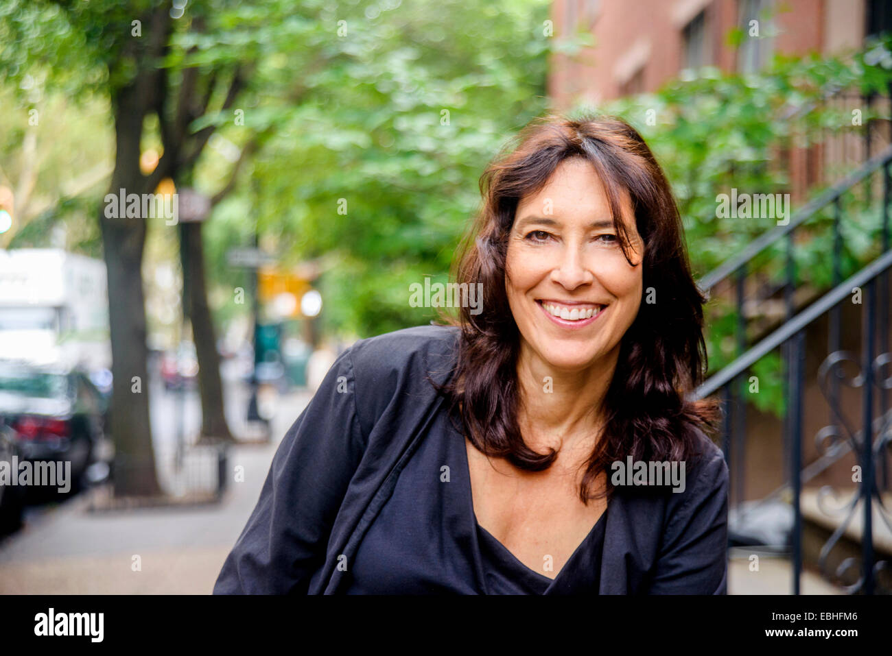 Portrait of smiling mature woman on city street - Stock Image