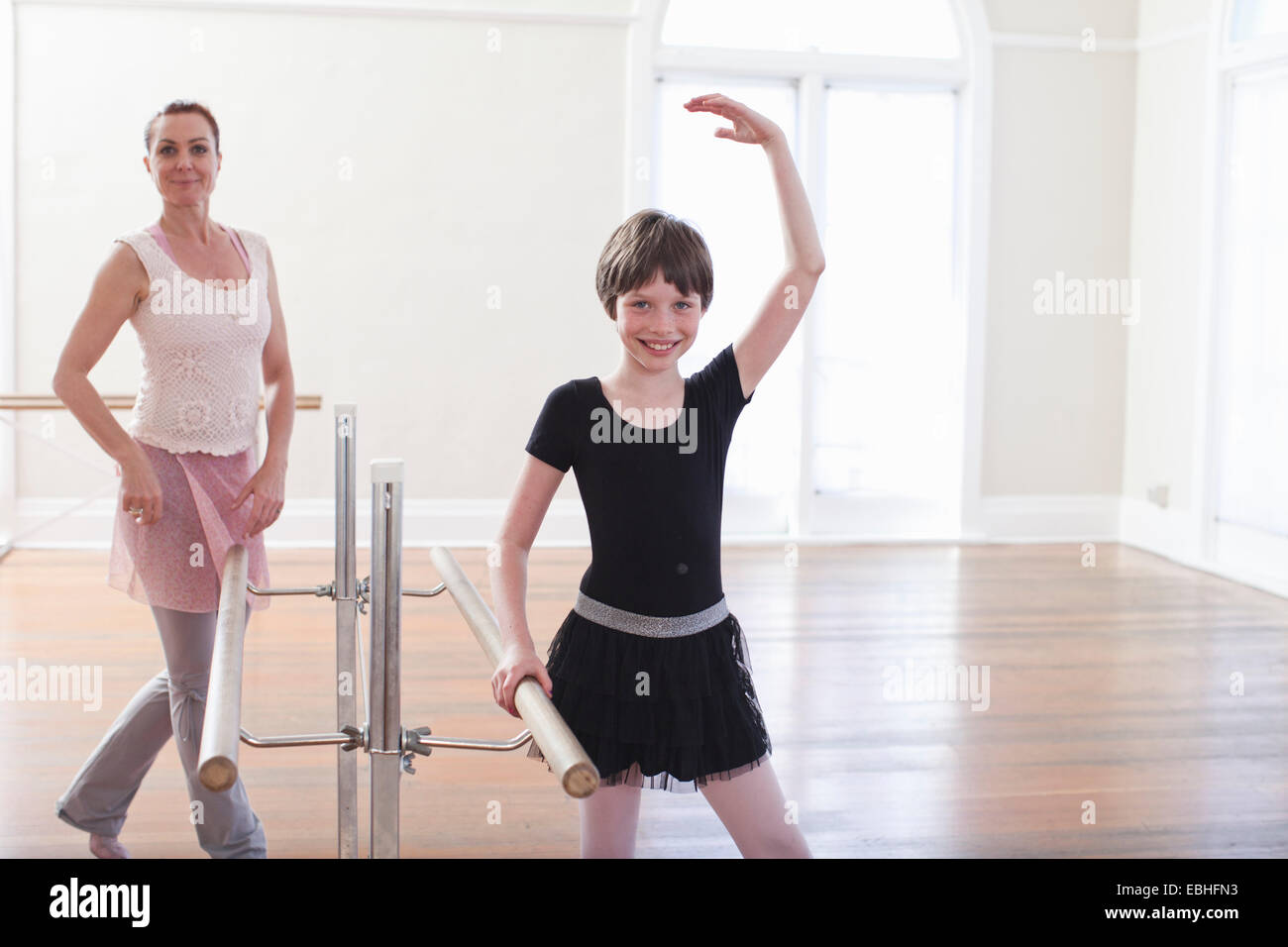 Girl practicing ballet with teacher at the barre in ballet school - Stock Image