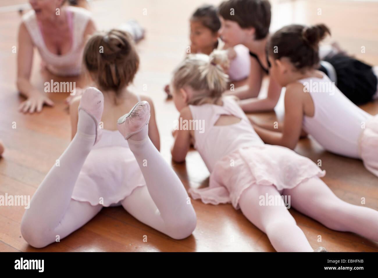 Children lying on floor practicing ballet in ballet school - Stock Image
