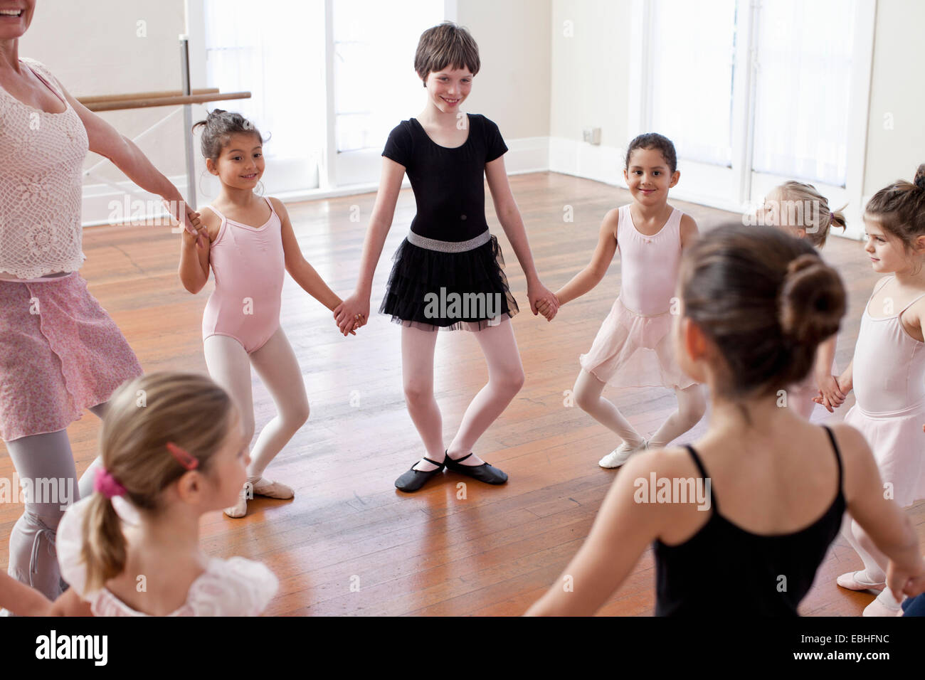 Children and teacher in a circle practicing ballet in ballet school - Stock Image