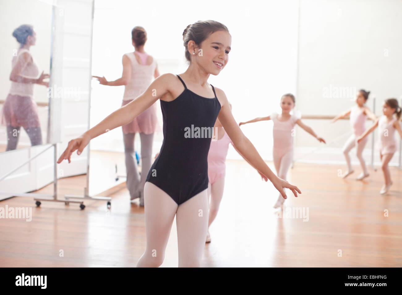 Teacher and girls practicing ballet dancing in ballet school - Stock Image