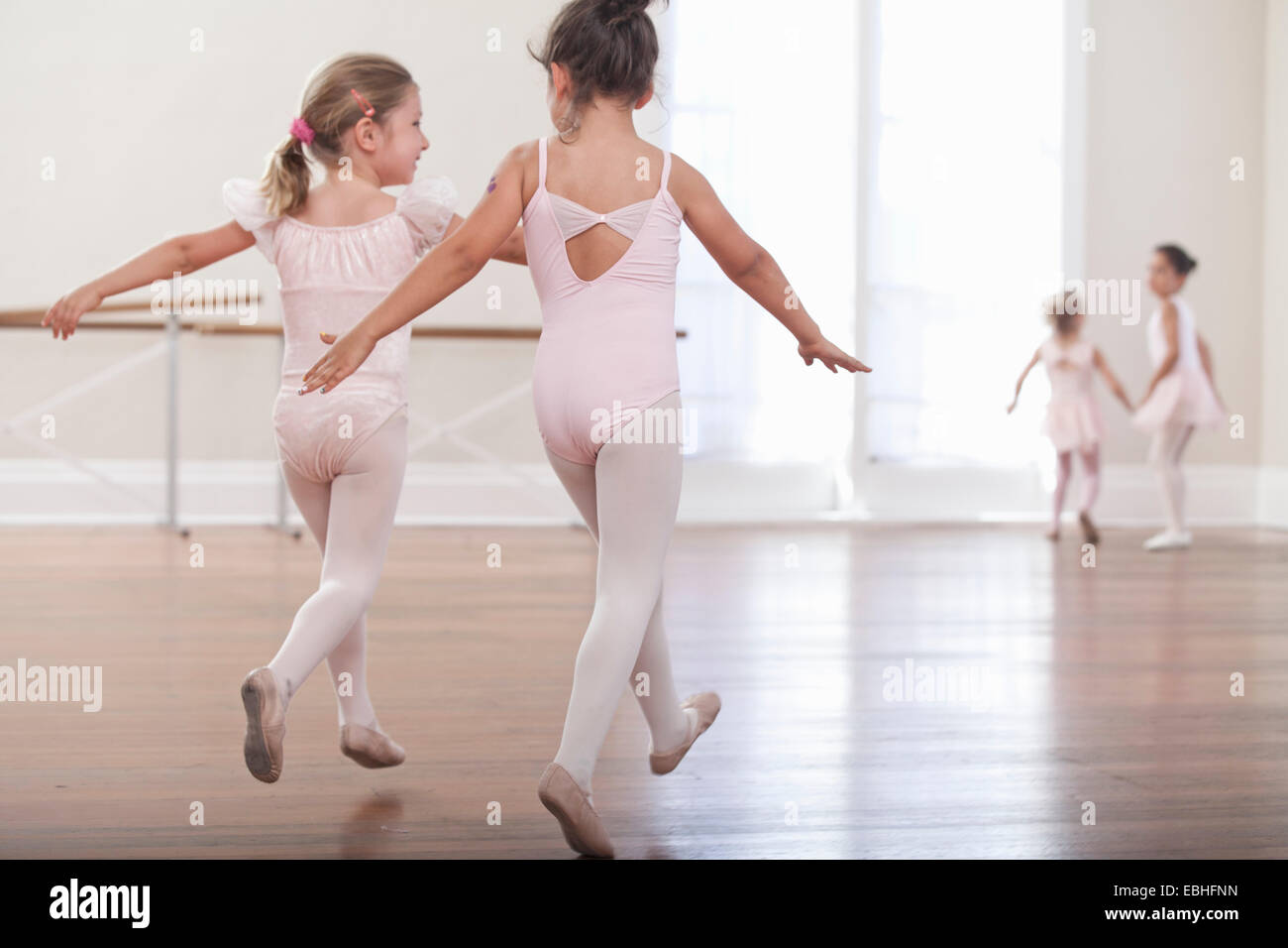Rear view of girls practicing jump in ballet school - Stock Image