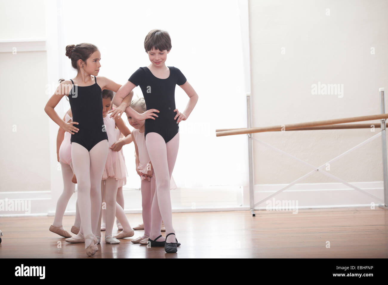 Group of girls practicing with hands on hips in ballet school - Stock Image