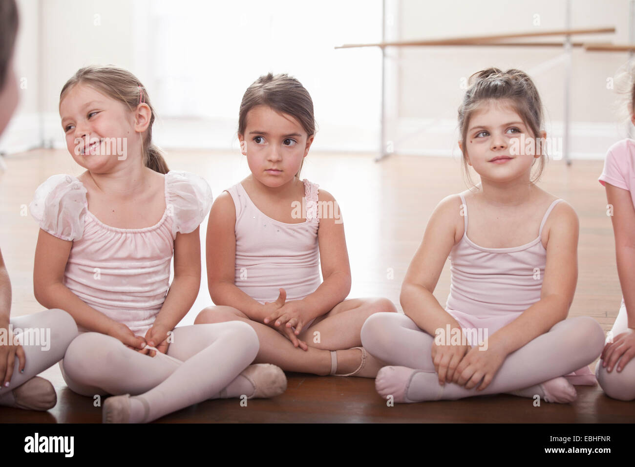 Group of girls sitting on floor in ballet school - Stock Image