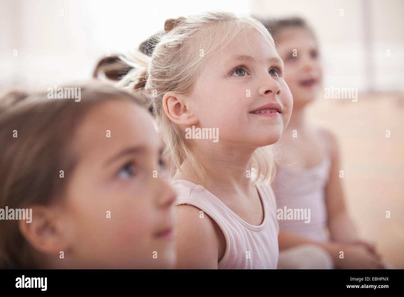 Group of girls looking up in ballet school - Stock Image