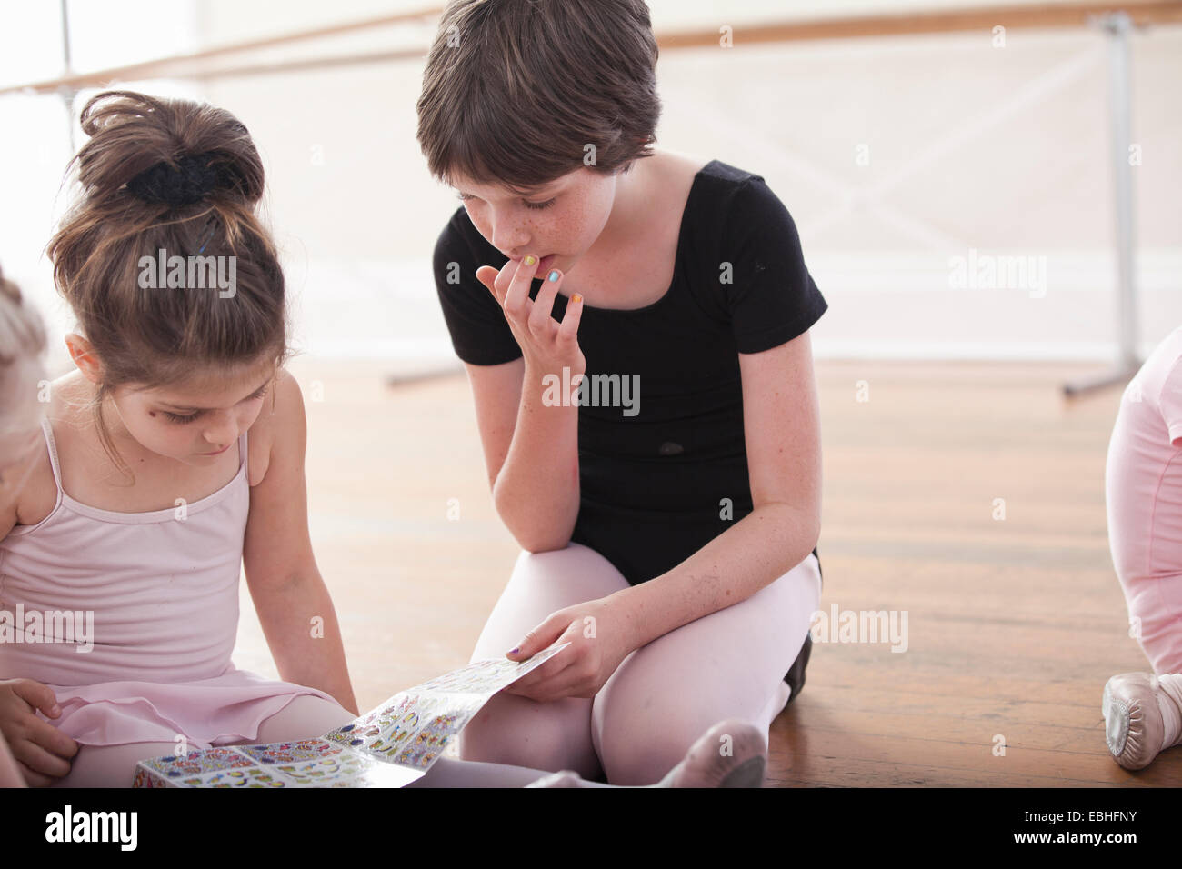 Girls swapping stickers in ballet school - Stock Image