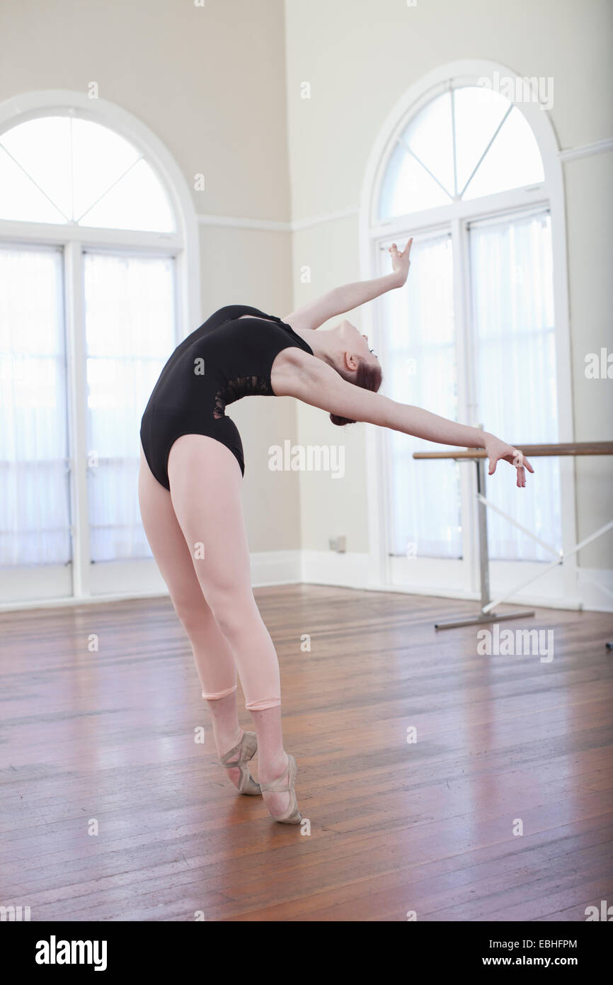 Teenage ballerina leaning back in ballet position at ballet school - Stock Image