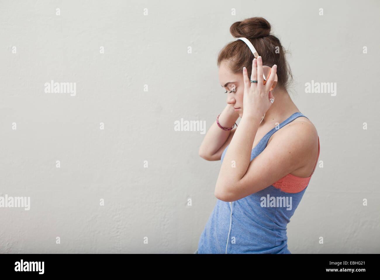 Teenage girl listening to music on headphones in ballet school - Stock Image
